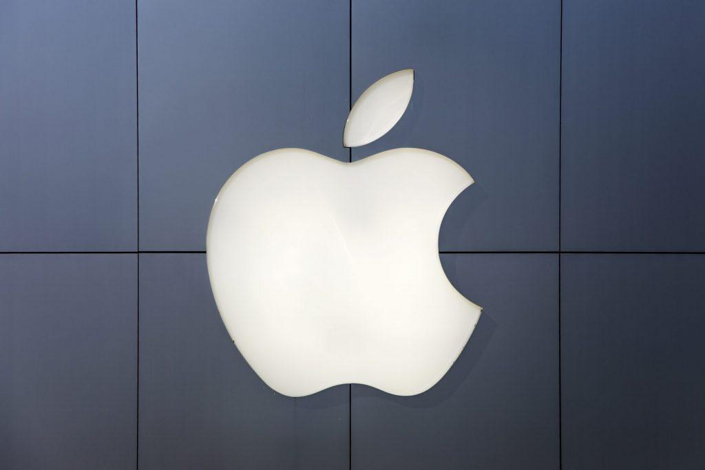 Post mit beleuchtetem Apple Logo auf dunkler Wand