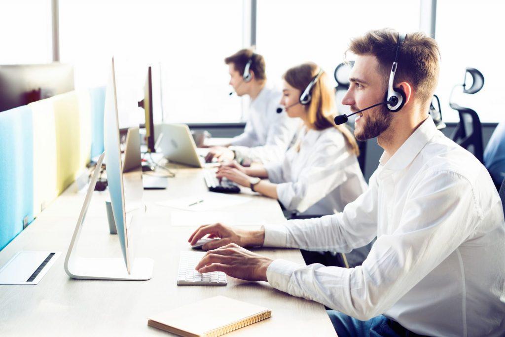 Mitararbeitende eines Callcenters telefonieren am Computer.